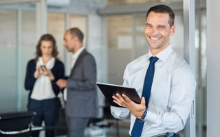 Happy businessman holding digital tablet with team discussing project in the background. Portrait of a confident business man holding computer laptop. Successful young business man at the office.